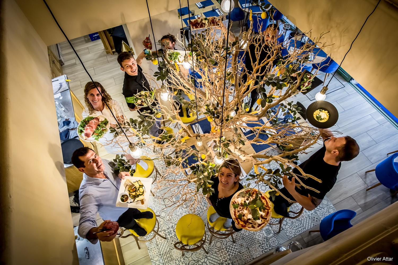 Image représentant une partie de l'équipe du restaurant. Ils se trouvent autour du citronnier de l'entrée. Ils tiennent un plat proposé par le Casa Leya dans leur main comme une pizza, des pâtes ou encore des salades.